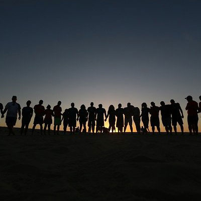 Silhouette of people in various poses against a sunset background