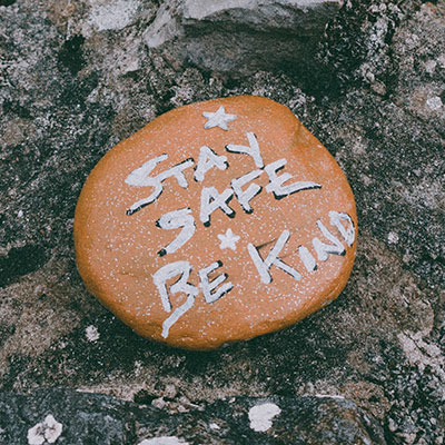 "A rock with the words ""stay safe, be kind"" painted on it"