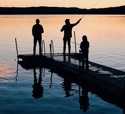 Family fishing on a dock at sunset.